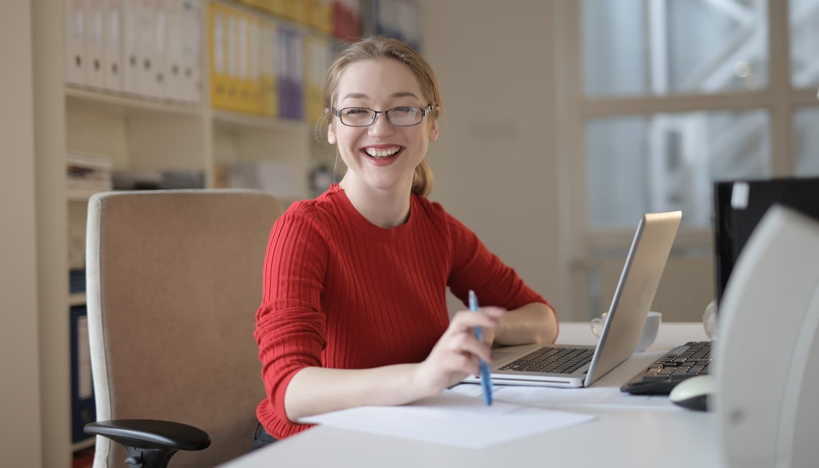 Student smiling while typing on her laptop