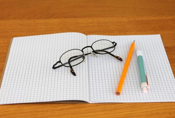 Glasses on graph paper with pencil and pen