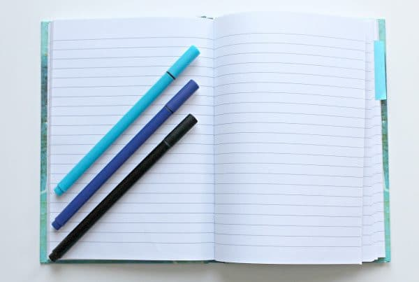 Blue empty notebook open with three blue pens