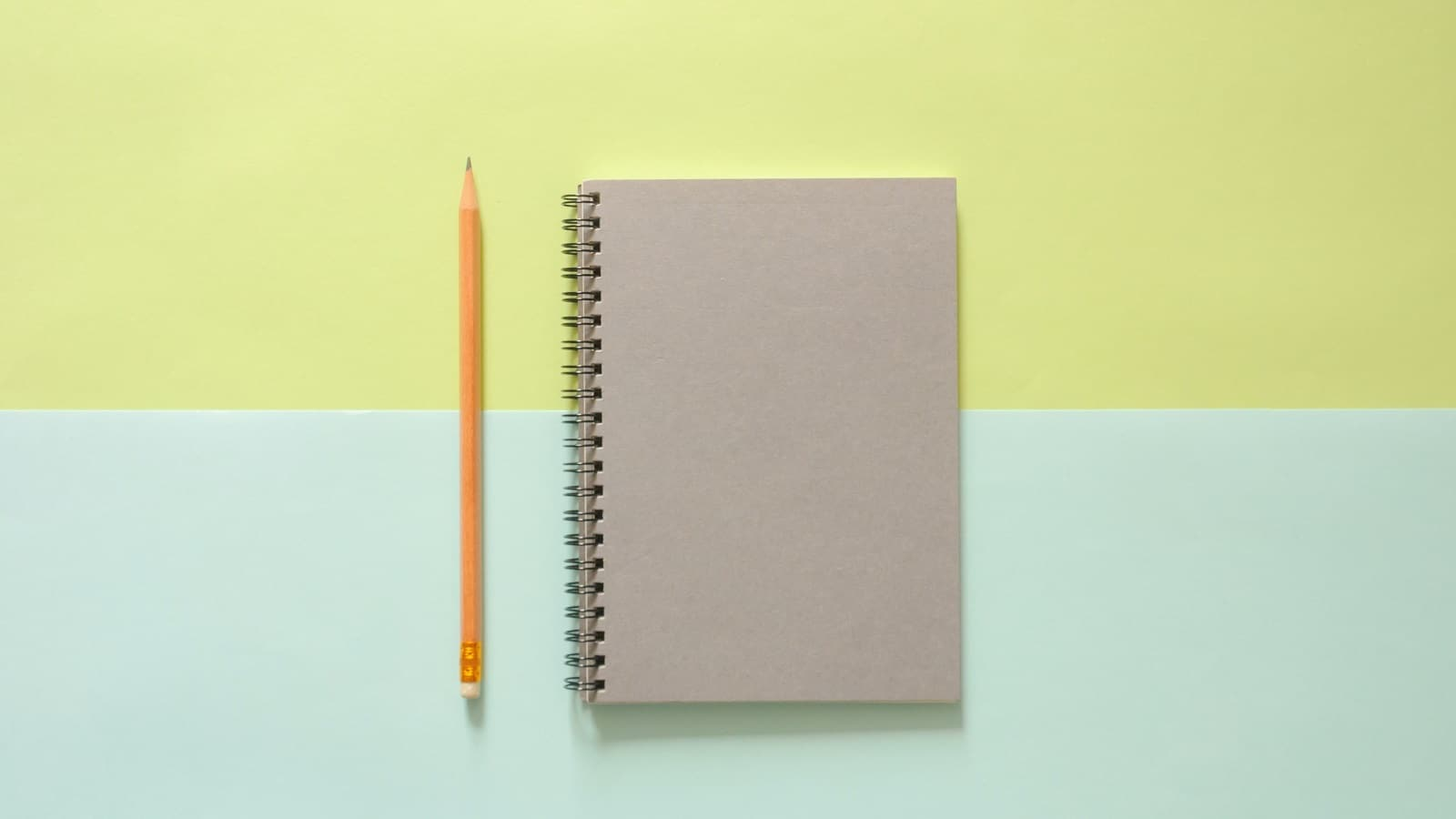 Closed notebook with pencil on green and blue background