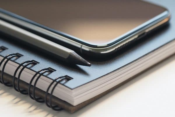 Phone on top of blue notebook with black pencil