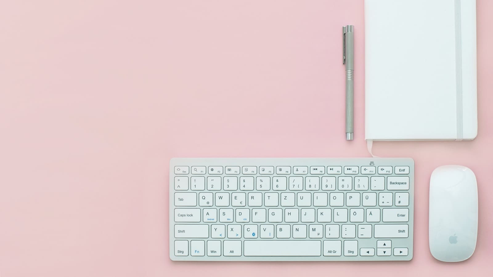 Wireless keyboard, wireless mouse, notebook and pen on a pink table