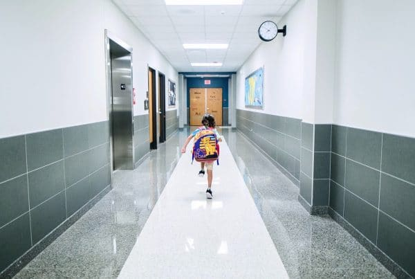 Child in backpack skipping down empty hallway