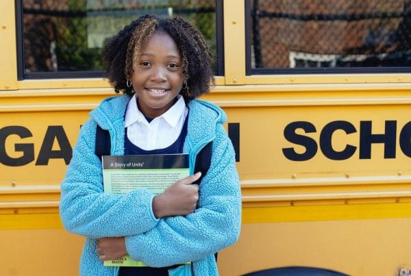 Schoolgirl hugging textbook in front of yellow school bus