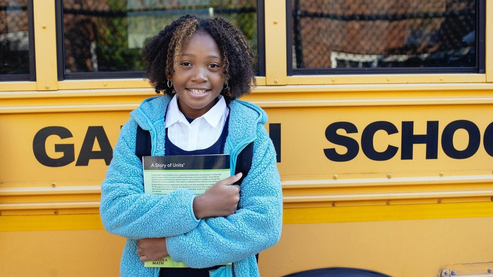 Schoolgirl hugging textbook in front of yellow school bus