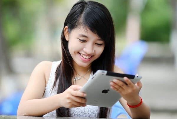 Girl smiling looking at iPad