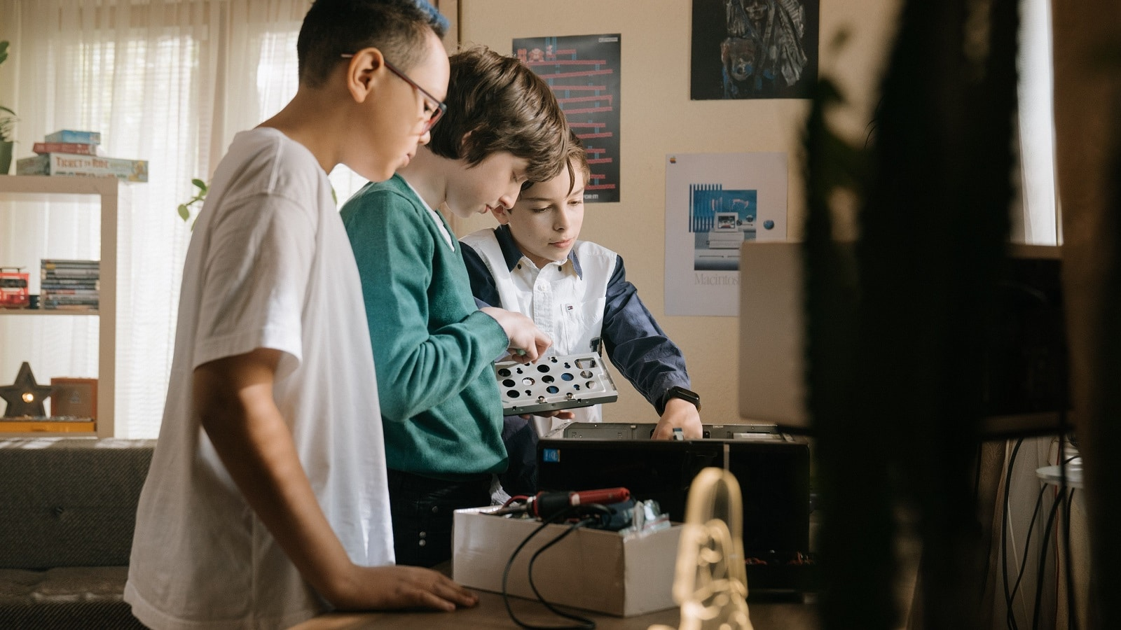 Three young students study a computer system