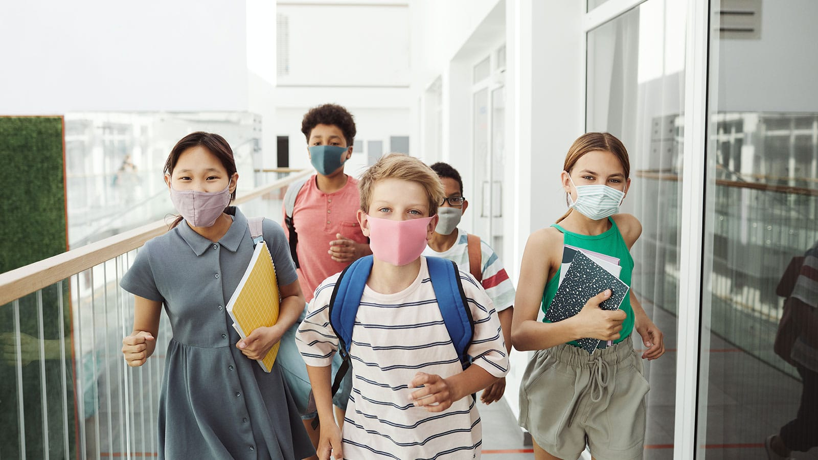 Five young students walking the hallways